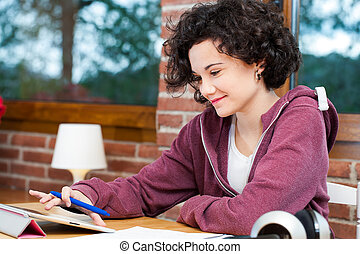 Young girl working on tablet - Cute young female teen doing...