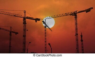 construction cranes working on background of setting sun -...