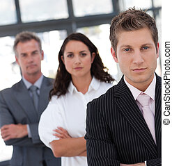 Serious Resolute and Confident Businessman in from of team