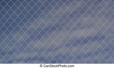 Chain link wire fence against cloudy sky timelapse