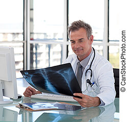 Mature Doctor looking at an x-ray - Mature Doctor looking at...