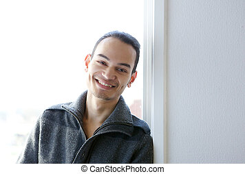 Young asian man smiling at home