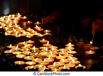 hands of an elderly woman lighting a candle