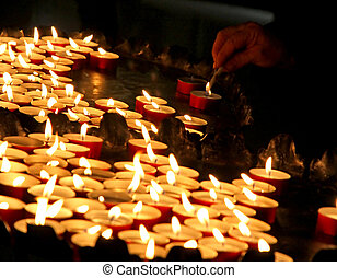 elderly woman lighting a candle in a church