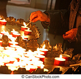 hands of an elderly woman lighting a candle in a church