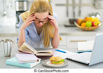 Stressed young woman studying in kitchen