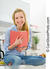 Smiling young woman reading book in kitchen