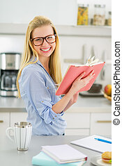 Smiling young woman studying in kitchen