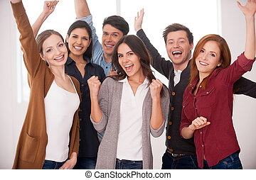 Happy business team. Group of cheerful young people standing close to each other and keeping arms raised
