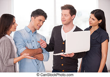 Discussing project together. Group of young people discussing something while one man holding laptop