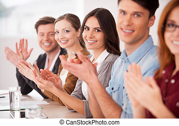 Applauding to you. Group of young people sitting together at the table and applauding to you