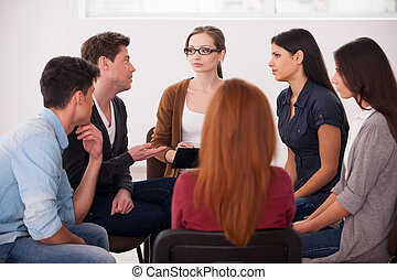 Group therapy. Group of people sitting close to each other...
