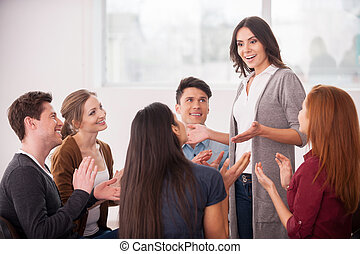 I have an issue. Group of people sitting close to each other while man telling something and gesturing