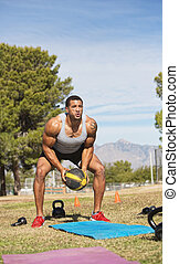 Male Exercising with Medicine Ball - Single man squatting...