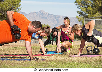 Adults in Boot Camp Fitness - Young woman working with...