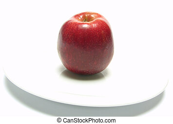 Red apple on a white plate