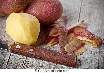 healthy organic peeled potatoes on wooden background
