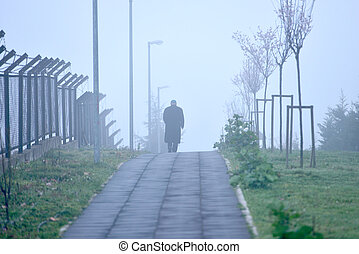 A man walking down the road in foggy weather