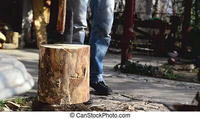 Lumber jack man chopping wood logs with ax. Making firewood...