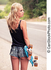 Beautiful young girl hipster with skateboarding in the...