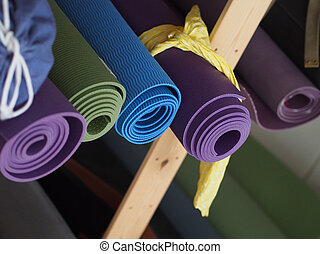 Yoga Mats  - Yoga mats in different colors in a shelf