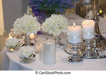 Table decorated with candles, hydrangeas and white roses