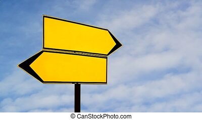 Two opposite direction signs against blue sky timelapse