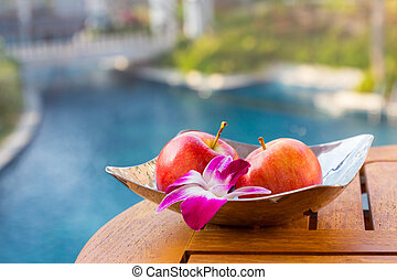 Bright apple with orchid in plate on the table over natual...