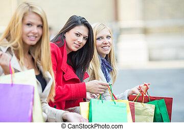 Friends shopping - Beautiful young women sitting after...