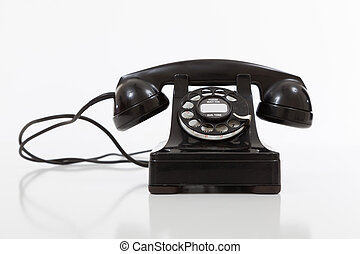 Black, vintage rotary phone on white - A black, vintage...