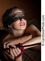 Beautiful girl blindfolded posing with hands bound -...