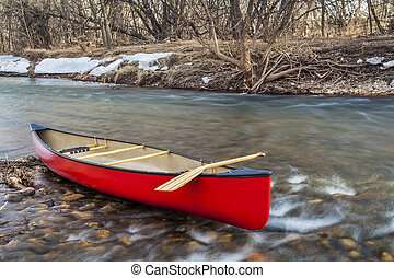 red canoe on a river - red canoe with a wooden paddle on...