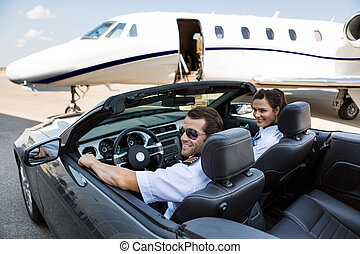Pilot And Airhostess In Convertible Against Private Jet -...