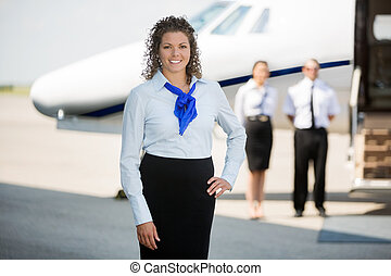 Airhostess With Hand On Hip Standing At Airport Terminal -...