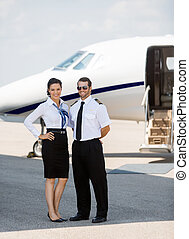 Stewardess And Pilot Standing Against Private Jet - Full...