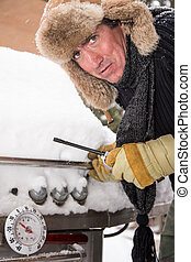 Cold BBQ Start - A man bundled up with a scarf and fur hat...