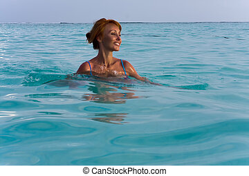 The happy woman in the sea waves