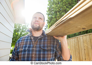 Carpenter Carrying Planks While Looking Away At Site - Mid...