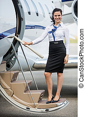 Stewardess Standing On Ladder Of Private Jet - Full length...