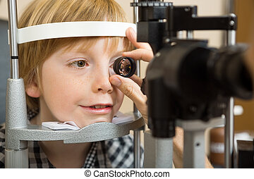 Optician's Hand Checking Boy's Eye With Lens - Closeup of...