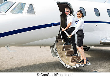 Stewardess And Pilot Boarding Private Jet - Portrait of...