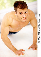 Well Shaped - Muscular and tanned male is excersing, wearing...