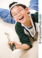 Winning boy with his medal and trophy - An asian boy excited...