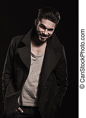 relaxed fashion man with beard smiling, hands in pockets -...