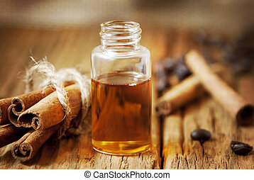 Essence Bottle and Cinnamon Sticks on Wooden Board