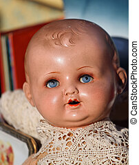 face of an old 1920s vintage doll for sale in antiques shop