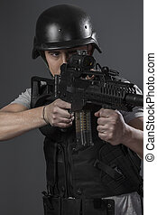 Playing, paintball sport player wearing protective helmet aiming pistol ,black armor and machine gun