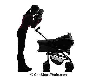 woman prams holding kissing baby silhouette - one caucasian...