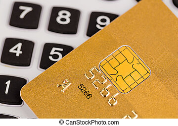 golden credit card and calculator - a gold credit card and a...
