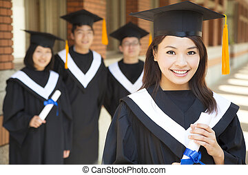 beautiful  college graduate holding diploma with classmates